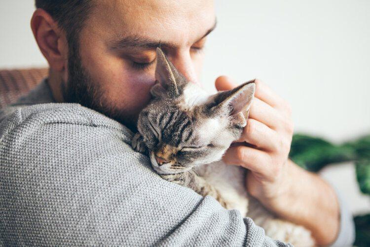 man cuddling cat