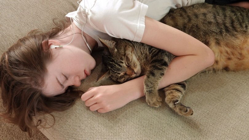 A young teen girl naps on the couch, hugging her cat