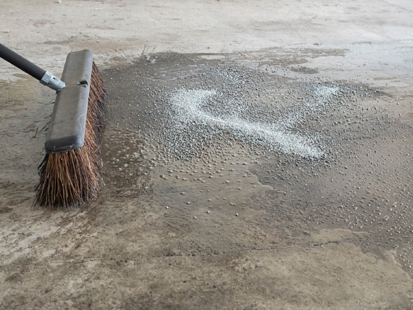 a broom and water cleans up an oil spill