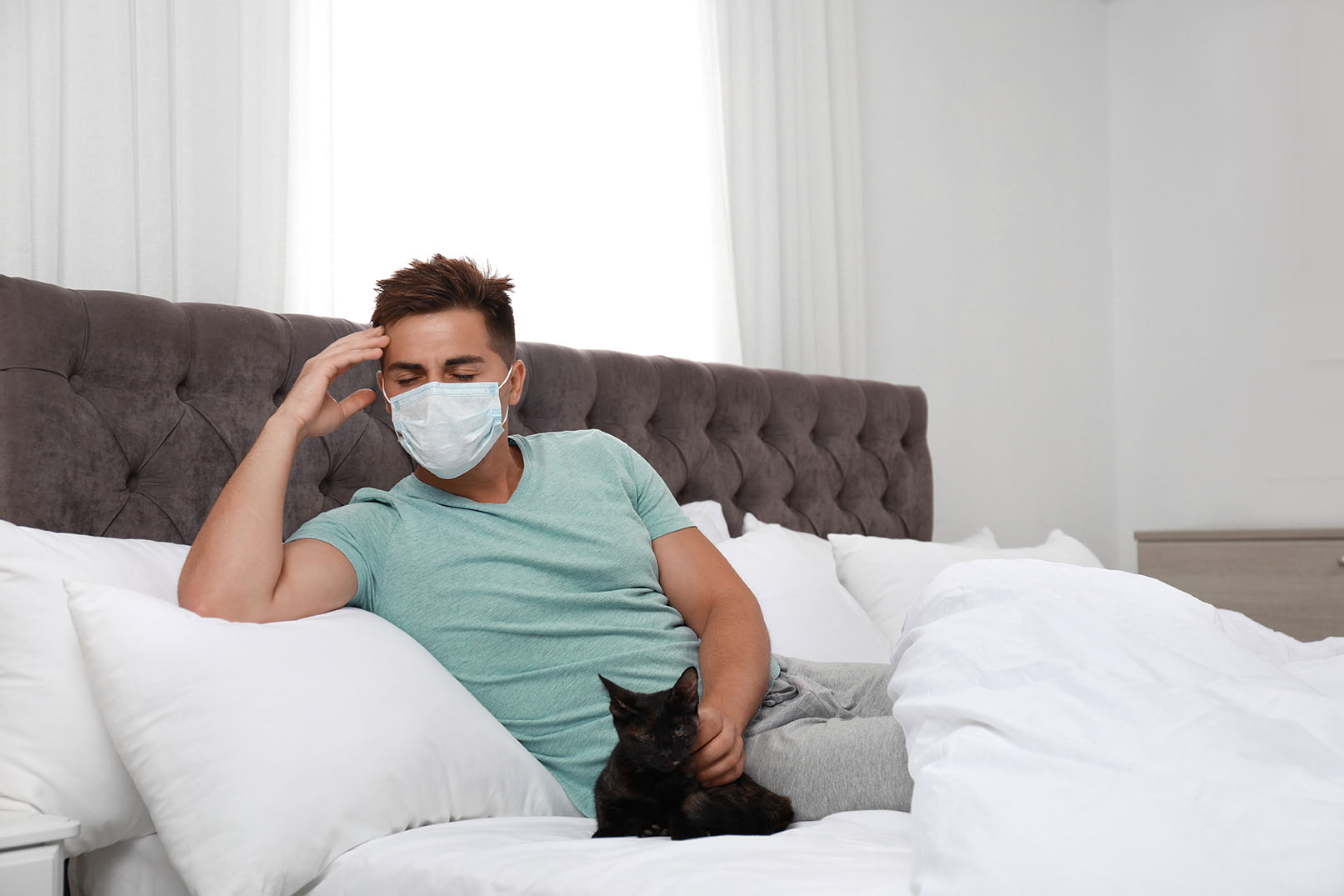 man sick with cat beside him