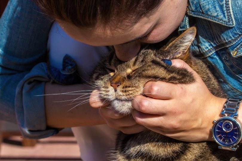 woman cuddling a cat